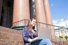 Hipsterflickakeyboarding på netto-boken som vilar nära högskolan eller arkitektonisk byggnad arkivfoton