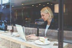 Hipsterflickan använder netto-boken under vilar i kafé arkivfoton