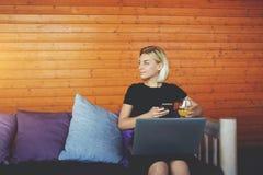 Hipsterflickan ser på hennes vänner, medan sitter med mobiltelefon- och bärbar datordatoren i kafé royaltyfria foton