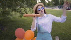 Hipsterflickan som sjunger med en franskbröd som en mikrofon i sommar, parkerar, har picknick stock video