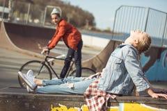 Hipsterflickan som vilar på skateboarden, parkerar medan pojkeridningcykeln Fotografering för Bildbyråer