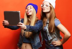 Hipsterflickavänner som tar selfie med den digitala minnestavlan, studio Royaltyfri Foto
