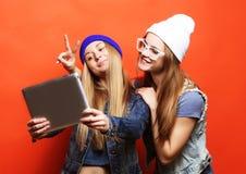 Hipsterflickavänner som tar selfie med den digitala minnestavlan, studio Royaltyfria Bilder