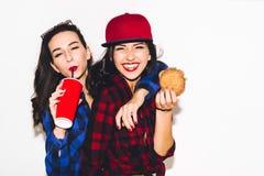 Hipsterflickor med den vegetariska hamburgaren som dricker en sodavatten från sugrör och har gyckel som är lycklig, ler och skrat royaltyfri fotografi