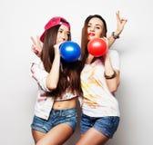 Hipsterflickor som ler och rymmer färgade ballonger Royaltyfri Bild