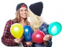 Hipsterflickor som ler och rymmer färgade ballonger Royaltyfria Foton