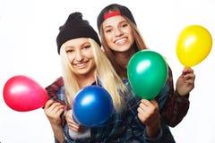 Hipsterflickor som ler och rymmer färgade ballonger Arkivfoto