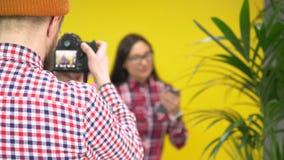 Hipsterfotograf som tar bilden av modellen för blandat lopp i kafé lager videofilmer