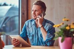Hipstergrabben med en stilfullt frisyr och skägg sitter på en tabell i ett vägrenkafé och att tala på telefonen och hållna en min arkivfoto