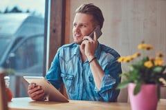 Hipstergrabben med en stilfullt frisyr och skägg sitter på en tabell i ett vägrenkafé och att tala på telefonen och hållna en min arkivfoton