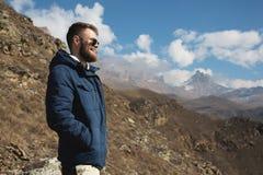 Hipsterhandelsresanden i ner en klå upp och solglasögonställningar på en berglutning mot bakgrunden av epos vaggar och fotografering för bildbyråer