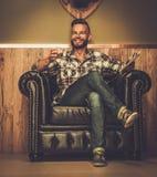 Hipsterin Lederstuhl von mittlerem Alter wird Glas Whisky Stockfoto
