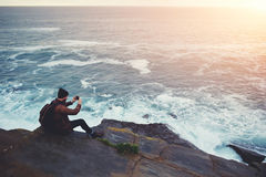 Hipsterkerel die beelden van verbazend landschap op mobiele slimme telefoon digitale camera nemen terwijl het zitten op een rots  Royalty-vrije Stock Afbeelding