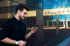 Hipsterkerel het typen tekst op smartphone tijdens online het leren op netbook stock afbeeldingen