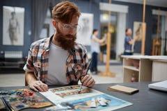 Hipsterkunstenaar Painting Pictures in Art Class stock fotografie