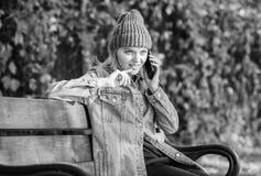 Hipsterkvinna att tala p? telefonen Flickan har mobiltelefonkonversation parkerar in koppla av p? b?nk, i srpring V?nta p? arkivbilder
