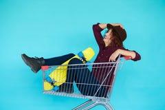 Hipsterkvinna med gult skateboardsammanträde i shoppingspårvagn Royaltyfria Bilder