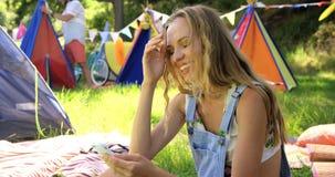 Hipsterkvinna som ser hennes mobiltelefon arkivfilmer