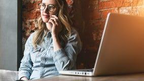 Hipsterkvinna som sitter i kafét som lutar på tegelstenväggen och talar på mobiltelefonen Flickan kallar taxien, gör beställning  arkivbilder