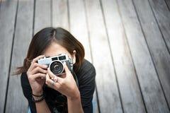 Hipsterkvinnan som tar foto med den retro filmkameran på träfloorofstad, parkerar, den härliga flickan som fotograferas i den gam arkivfoton