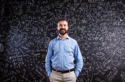 Hipsterlärare mot den stora svart tavla med matematiska symboler Royaltyfri Bild