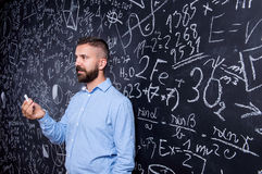 Hipsterlärare mot den stora svart tavla med matematiska symboler Royaltyfri Foto
