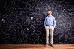 Hipsterlärare mot den stora svart tavla med matematiska symboler Fotografering för Bildbyråer