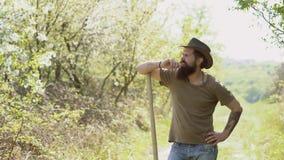 Hipsterlandbouwer het ontspannen bij aardachtergrond Ecobedrijfsmedewerker Het Amerikaanse landbouwbedrijfleven Het concept van d stock video
