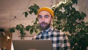 Hipsterman i gul hatt genom att använda video pratstund på bärbar datordatoren för att meddela med vänner eller affärspartners stock video
