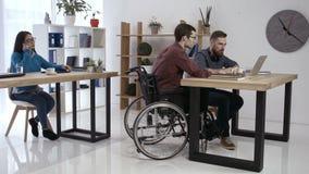 Hipsterman i rullstolen som i regeringsställning arbetar stock video