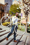 Hipsterman i solglasögon som på bär hans skuldracykel på gatatrappa En ung stilig man med skägginnehavcykeln på hans righ royaltyfri fotografi