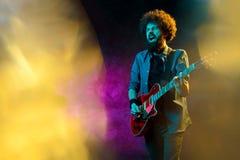 Hipsterman med lockigt h?r med den r?da gitarren i neonljus leka rock skjuten studio f?r elektrisk gitarrmusiker royaltyfria foton