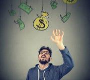 Hipsterman som försöker att gripa en säck av pengar arkivbild