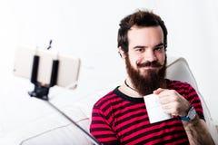 Hipsterman som tar en selfie med hans pinne fotografering för bildbyråer