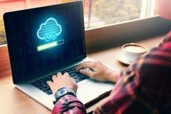 Hipstermanhand genom att använda bärbara datorn med molnet som beräknar och laddar upp Arkivfoto