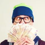 Hipstermannen i exponeringsglas täckte framsidan med pengar som åt sidan ser Grabb i hatten som har fanen av pengar i hand på den royaltyfria bilder