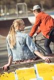 Hipstermeisje die bij skateboardpark rusten terwijl jongens berijdende fiets Royalty-vrije Stock Afbeelding
