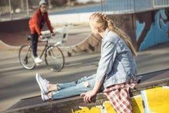 Hipstermeisje die bij skateboardpark rusten terwijl jongens berijdende fiets Stock Foto's