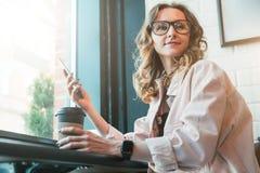Hipstermeisje die in glazen in koffie dichtbij venster, het drinken koffie zitten en het gebruiken van smartphone stock foto's