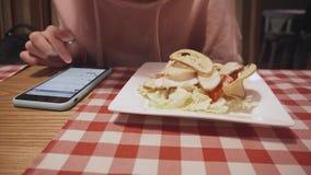 Hipstermeisje die salade eten bij restaurant en op smartphone texting stock videobeelden