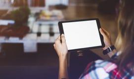 Hipstermeisje die tablettechnologie in huisatmosfeer gebruiken, de holdingscomputer van de meisjespersoon met het lege scherm op  stock afbeeldingen