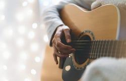 Hipstermeisje het spelen gitaar in een behaaglijke atmosfeer, persoon die op muzikaal instrument op illimination van gloed bokeh  stock foto