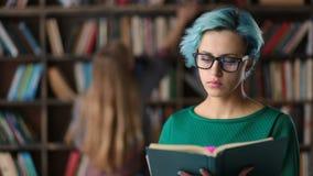 Hipstermeisje in lezingsboek wordt geabsorbeerd in bibliotheek die stock footage