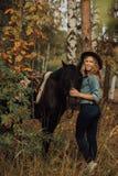Hipstermeisje met een paard in hout het glimlachen royalty-vrije stock afbeeldingen