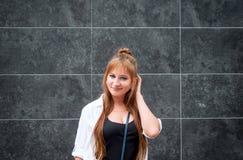 Hipstermeisje op een donkere steenachtergrond die een gebaar van dou maken stock afbeeldingen