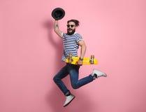 Hipstermens die met longboard springen stock foto