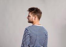 Hipstermens in gestreepte t-shirt, grijze achtergrond, studioschot Royalty-vrije Stock Foto