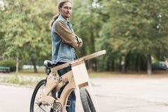 Hipstermens met zijn kruiser houten met de hand gemaakte fiets Royalty-vrije Stock Fotografie