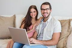 Hipsterpar genom att använda bärbara datorn på soffan Arkivfoton