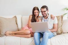 Hipsterpar genom att använda bärbara datorn på soffan Royaltyfri Bild